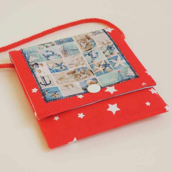 Dětská textilní kapsička červené barvy s aplikací obrázku s mořským motivem, s bavlněnou šňůrkou k pověšení na krk, zapínání na druk