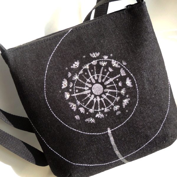 lehká černá kabelka z riflového materiálu se stříbrným potiskem chmýří pampelišky a bílým prošíváním