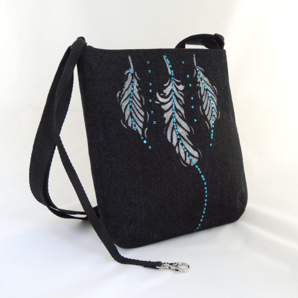 Lehká černá riflová kabelka se stříbrným potiskem peříček a bohatě zdobená drobnými modrými flitry, poutko s karabinkou na klíče