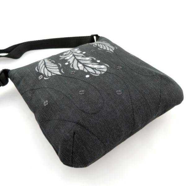 lehká textilní kabelka sportovního střihu z černého riflového materiálu s bílým ozdobným prošíváním s potiskem stříbrných peříček a s flitry