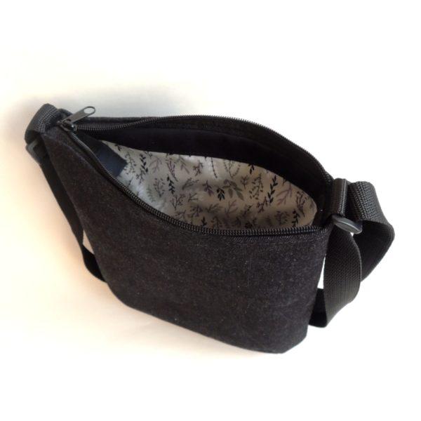 lehká textilní kabelka sportovního střihu z černého riflového materiálu s bílým ozdobným prošíváním a stříbrnou vážkou