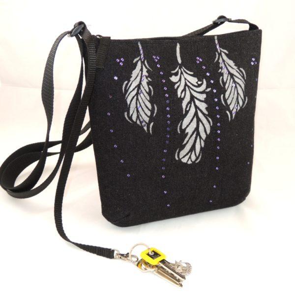 lehká textilní kabelka sportovního střihu z černého riflového materiálu s potiskem tří peříček a s flitry