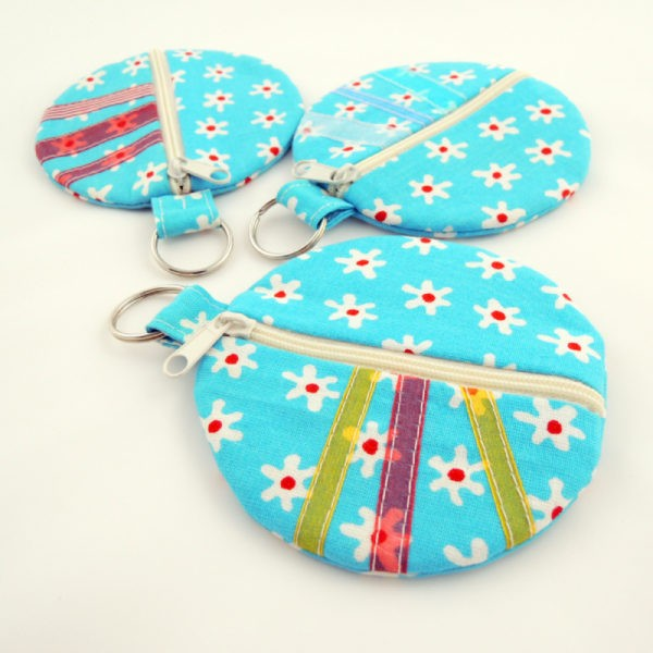 Textilní kulatá peněženka s kroužkem na pověšení, zapínání na zip. Veselé barvy.