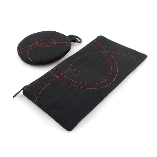 Aby byla kabelkasada sportovní kabelky, pouzdra a peněženky ve stejném stylu z černého softshellu s ozdobným prošíváním lehká, volila jsem minimum přihrádek a použila jsem plastové komponenty. Vnitřek kabelky je z bavlněné podšívky s kapsičkou na doklady. Součástí sady je pouzdro na mobil, tužky nebo brýle a také kulatá peněženka. Vše je zhotovené ve stejném stylu a ze stejného materiálu.