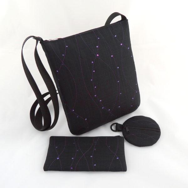 černá textilní kabelka crossbody, pouzdro na mobilní telefon a kulatá peněženka, zdobeno fialovým prošíváním a drobnými fialovými flitry