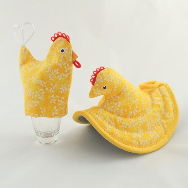 obal, čepička, punčoška, kulíšek na vajíčko je vyrobený ve stejném dizajnu jako kuchyňská chňapka slepička, vše v jasných žlutých odstínech s bílým potiskem jemných větviček, zobáček a červený hřebínek