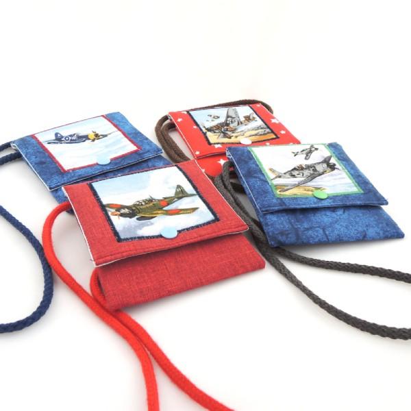 Dětské barevné kapsičky se šňůrkou na pověšení na krk a zapínáním na druk. Obrázek s motivem válečného letadla.